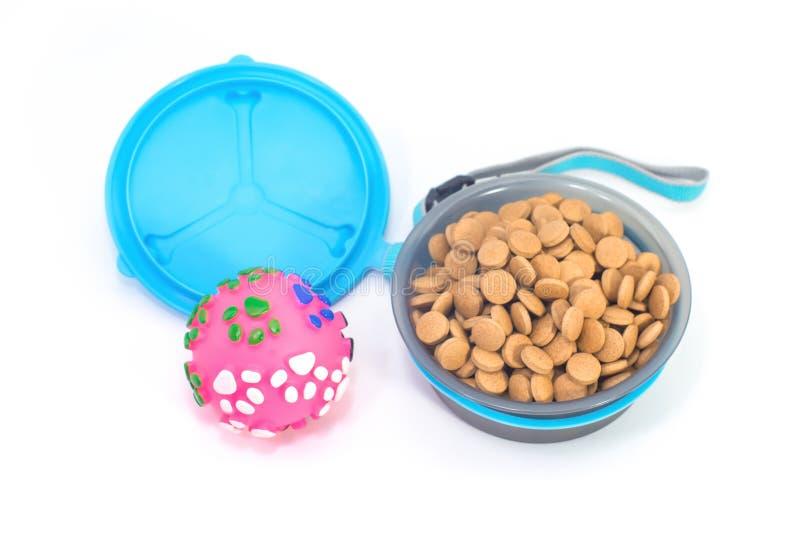 Bacia do animal de estimação com alimento e o brinquedo secos no fundo branco isolado fotos de stock royalty free