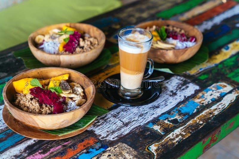 Bacia do batido feita com manga, banana, granola, o coco raspado, o fruto do dragão e a hortelã com café do latte foto de stock royalty free