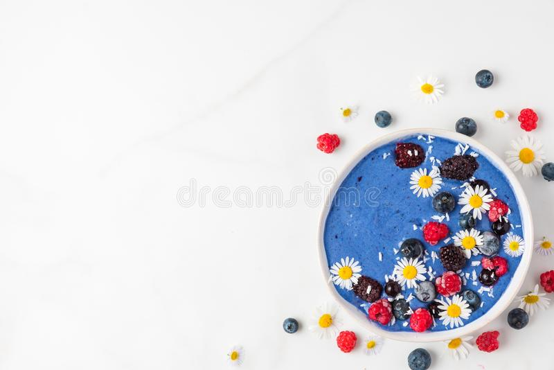 Bacia do batido ou creme agradável feita do spirulina azul, de bagas congeladas, de banana e de coco com flores da camomila foto de stock