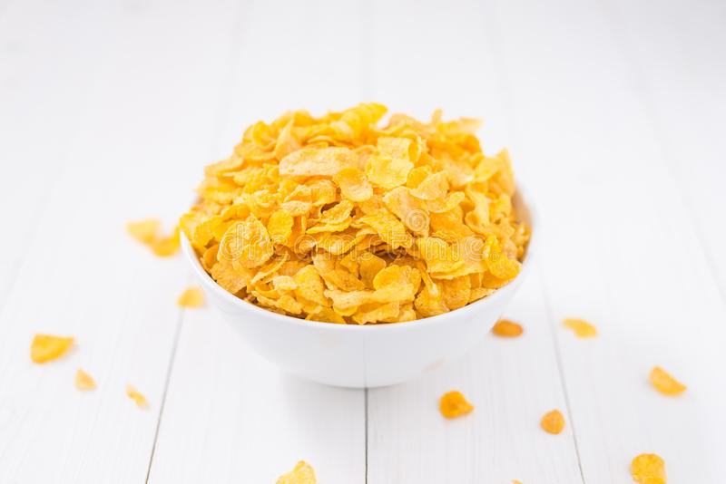 Bacia dos flocos de milho na tabela de madeira branca imagem de stock royalty free