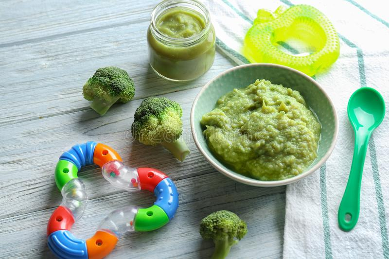 Bacia e frasco com comida para bebê saudável na tabela de madeira imagem de stock royalty free