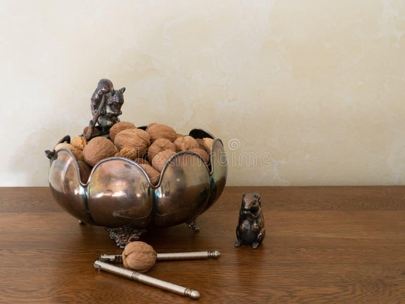 Bacia e quebra-nozes de prata decorativas com as porcas misturadas em Shell foto de stock