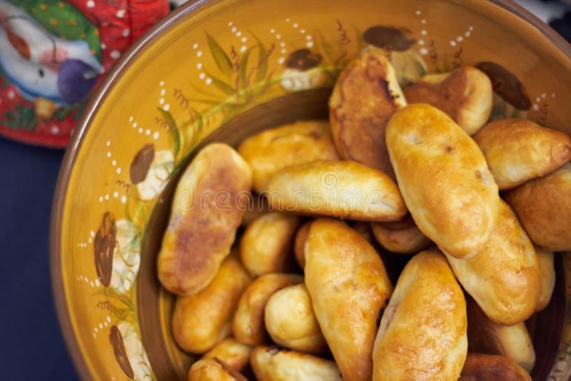 Bacia marrom letão tradicional da argila com tortas foto de stock