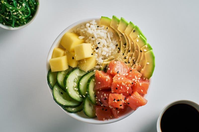 Bacia orgânica crua do puxão com salmões, abacate, arroz, manga, pepinos, salada do chuka e close-up do molho de soja no fundo br imagem de stock