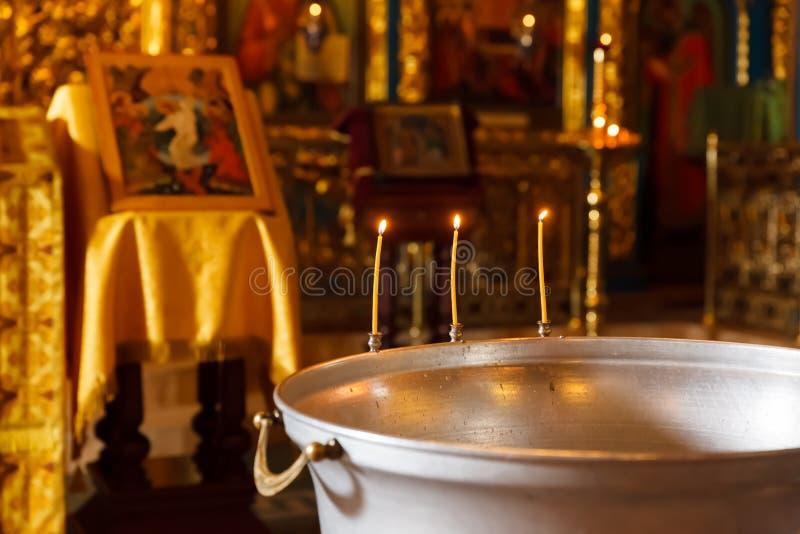 Bacia ortodoxo do batismo de água santamente e de velas fotografia de stock royalty free