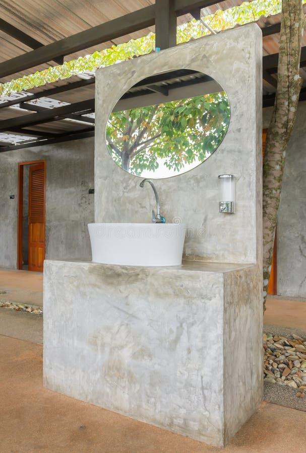 Bacia ou dissipador na base concreta com o espelho em Front Of Toilet imagens de stock