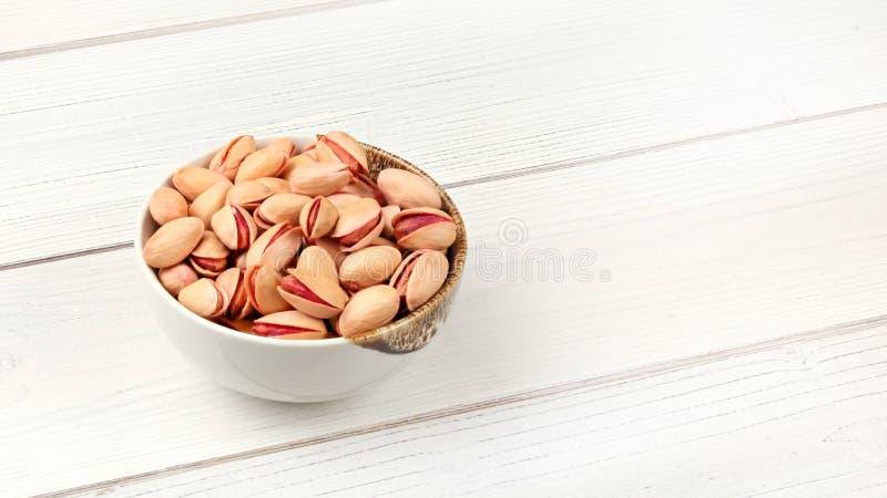 Bacia pequena com os pistaches na mesa das placas brancas, espaço para o texto no lado direito fotografia de stock royalty free