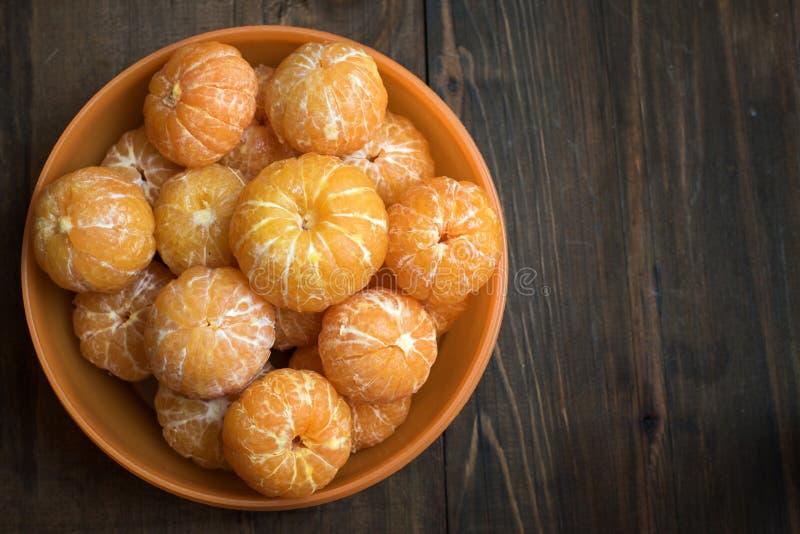 A bacia refinou os mandarino doces no fundo de madeira escuro imagem de stock