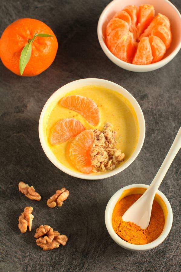 Bacia saboroso do batido da tangerina com frutos, cereais, sementes e pó da cúrcuma sobre o fundo cinzento imagem de stock
