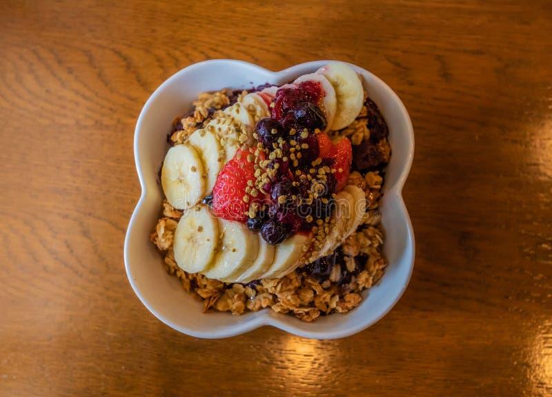 Bacia saudável da baga de Acai com fruto e granola imagem de stock