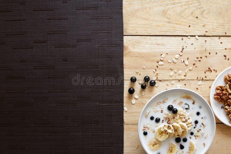 Bacia saud?vel do caf? da manh?: farinha de aveia com banana, sementes do chia, canela, nozes e mel fotos de stock royalty free