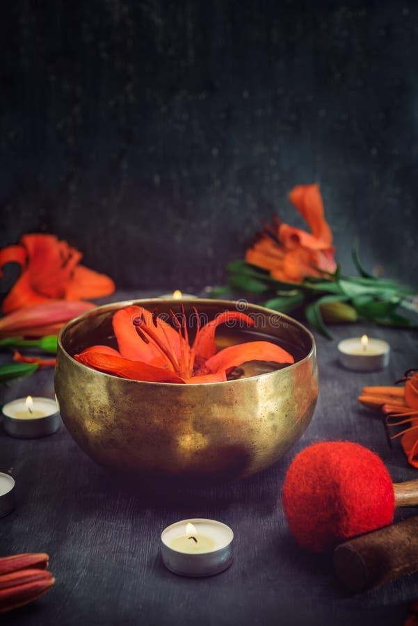 Bacia tibetana do canto com flutuação no lírio de água para dentro As varas especiais, as velas ardentes, as flores do lírio e as imagem de stock
