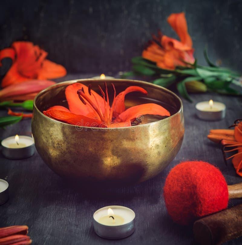 Bacia tibetana do canto com flutuação no lírio de água para dentro As varas especiais, as velas ardentes, as flores do lírio e as fotografia de stock royalty free