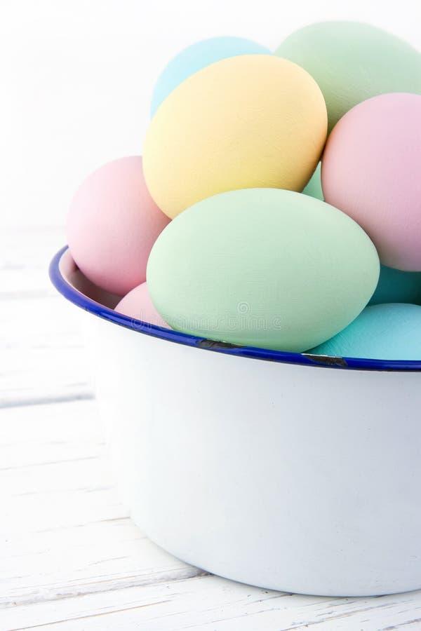 A bacia velha branca completamente de pastel coloriu ovos da páscoa foto de stock