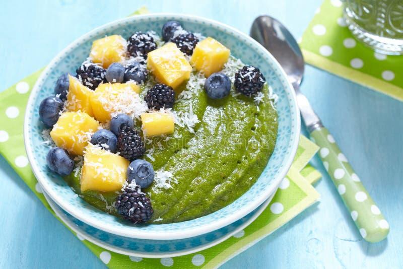 Bacia verde do batido do café da manhã coberta com frutos foto de stock