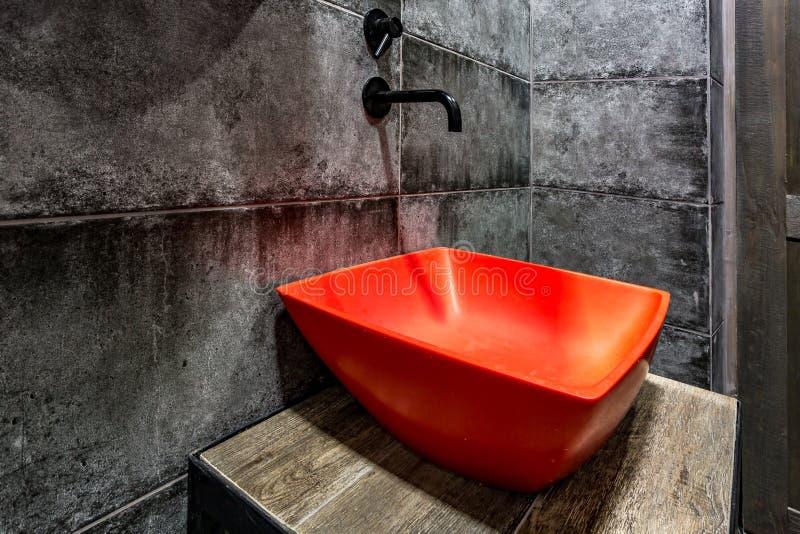 Bacia vermelha com o torneira no banheiro caro do s?t?o na barra de esporte da elite no fundo preto da parede de tijolo imagens de stock royalty free