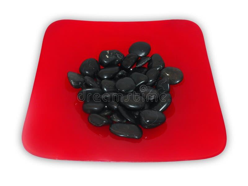 Bacia vermelha com pedras pretas fotos de stock royalty free
