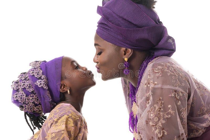 Baciare della ragazza del bambino e della madre Abbigliamento tradizionale africano Isolato fotografie stock