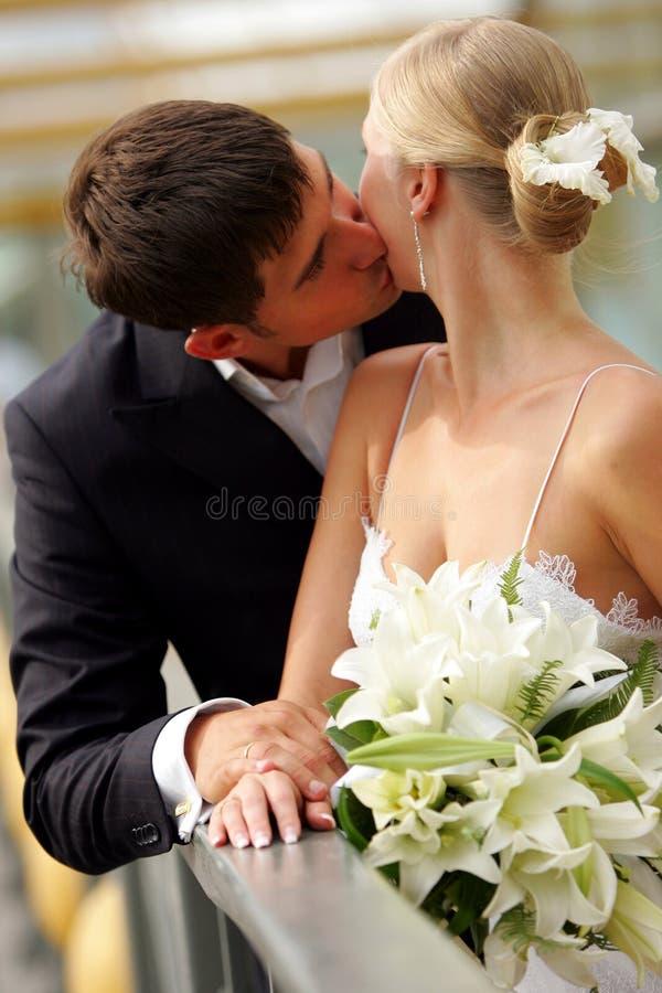 Baciare delle coppie del Newlywed fotografia stock
