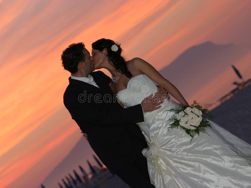 Baciare di tramonto della sposa e dello sposo fotografie stock