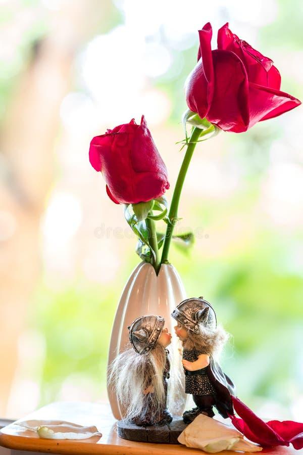baciare le bambole sotto due rose rosse con il fondo molle del fuoco immagini stock