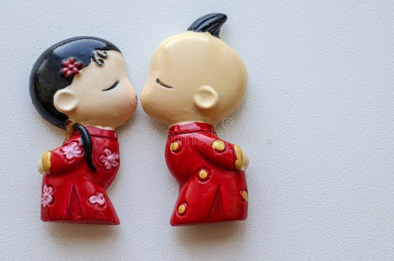Baciare le figurine di un ragazzo e di una ragazza in costumi cinesi nazionali fotografia stock