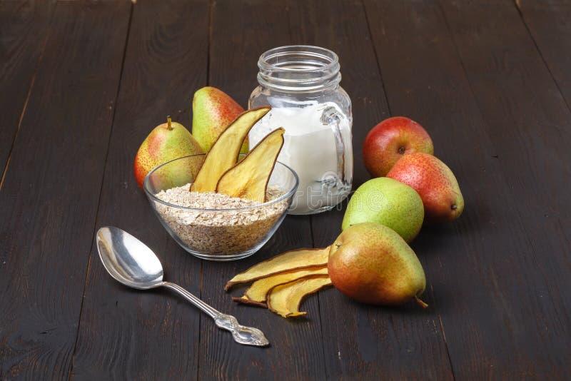 Bacias com café da manhã e as peras saudáveis em uma tabela de madeira Homema fotos de stock royalty free