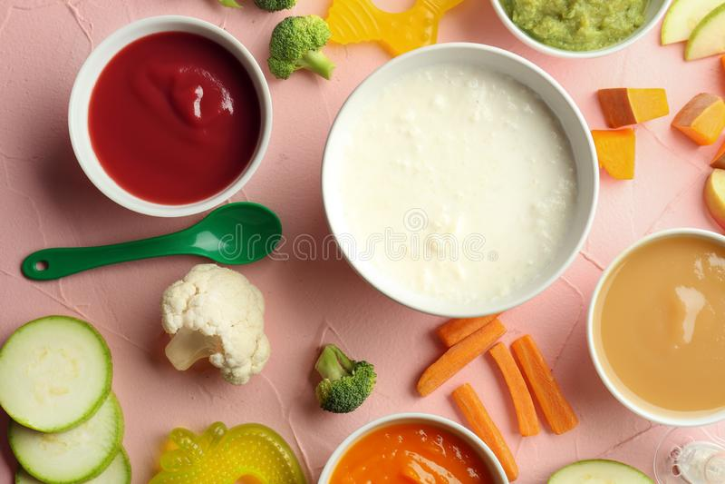Bacias com comida para bebê e os ingredientes saudáveis na tabela de cor fotos de stock royalty free