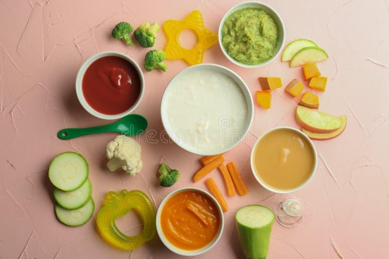 Bacias com comida para bebê e os ingredientes saudáveis na tabela de cor foto de stock royalty free