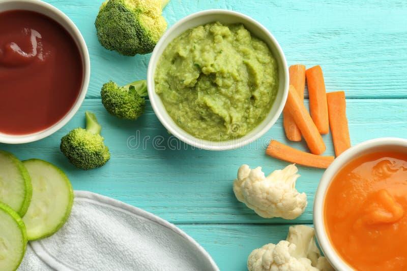 Bacias com comida para bebê e os ingredientes saudáveis na tabela de madeira da cor fotos de stock