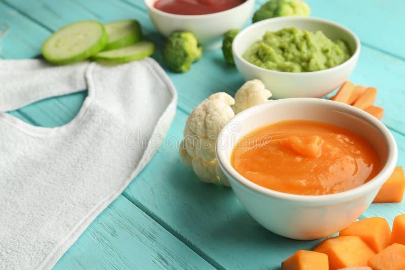 Bacias com comida para bebê e os ingredientes saudáveis na tabela de madeira da cor foto de stock royalty free