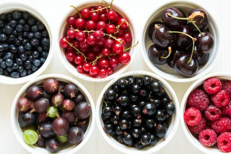 Bacias com a groselha madura fresca, o corinto vermelho, o corinto preto, a framboesa, o mirtilo e a cereja foto de stock