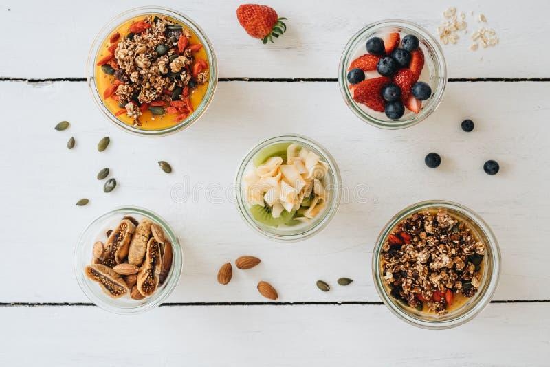 Bacias com iogurte, granola e frutos diferentes no fundo branco fotos de stock royalty free