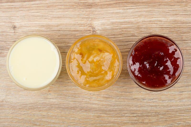 Bacias com leite condensado, doce do limão e doce de morango foto de stock royalty free