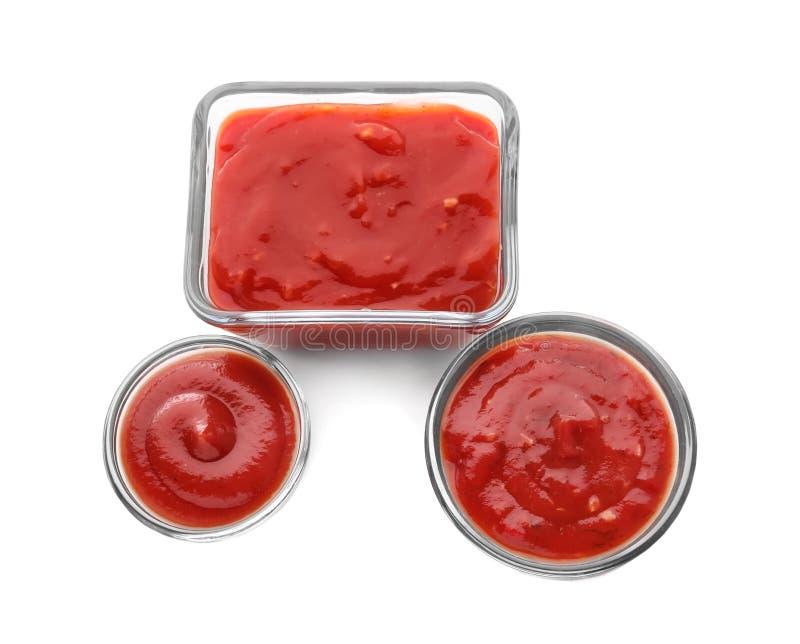 Bacias com molhos de tomate deliciosos no fundo branco fotografia de stock royalty free