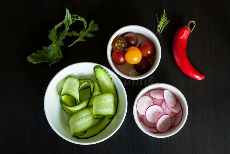 Bacias com os ingredientes para a salada imagem de stock
