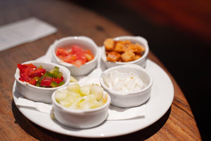 Bacias diferentes com partes pequenas de tomate fresco, de cebola, de pimenta, de pepinos e de algum pão torrado fotos de stock