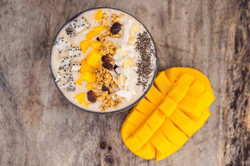 Bacias do batido feitas com manga, banana, granola, o coco raspado, o fruto do dragão, as sementes do chia e a hortelã no fundo d imagem de stock