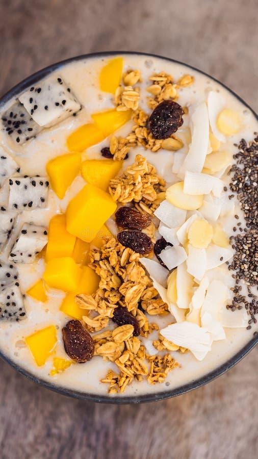 Bacias do batido feitas com manga, banana, granola, o coco raspado, o fruto do dragão, as sementes do chia e a hortelã no fundo d foto de stock