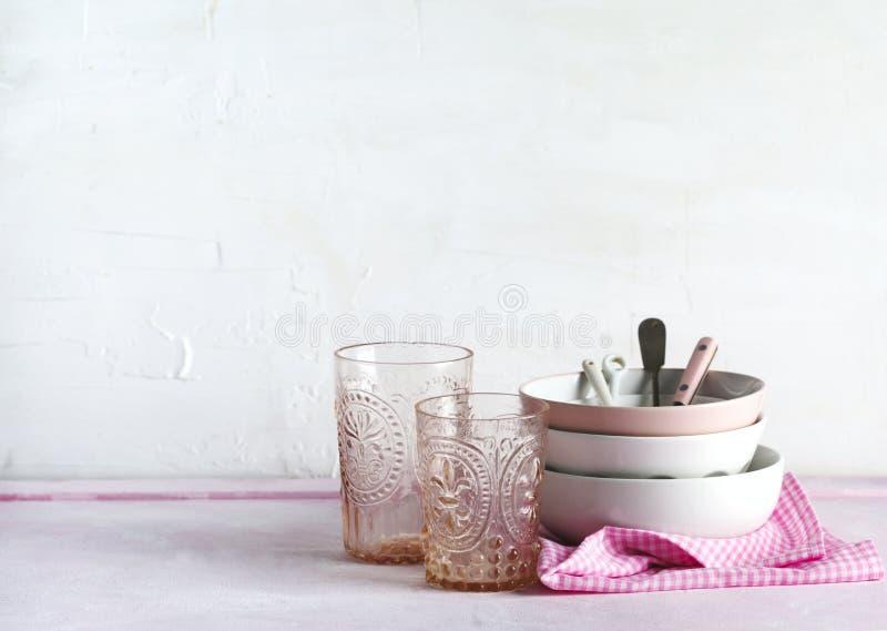 Bacias vazias do rosa e os brancos, vidros e utensílios da cozinha fotos de stock royalty free