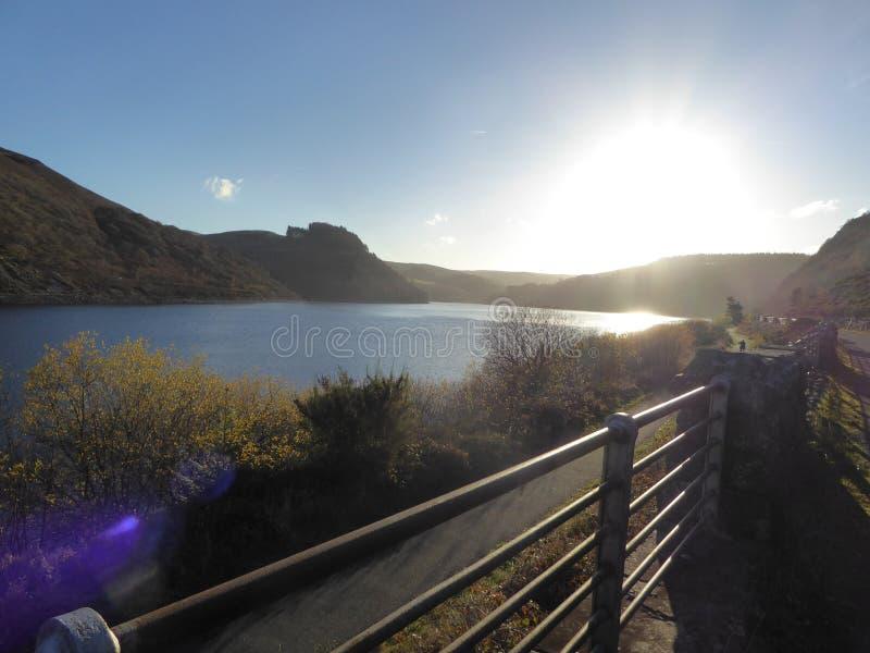 Bacini idrici di Elan Valley, Galles con il sole che va giù in cieli blu immagine stock