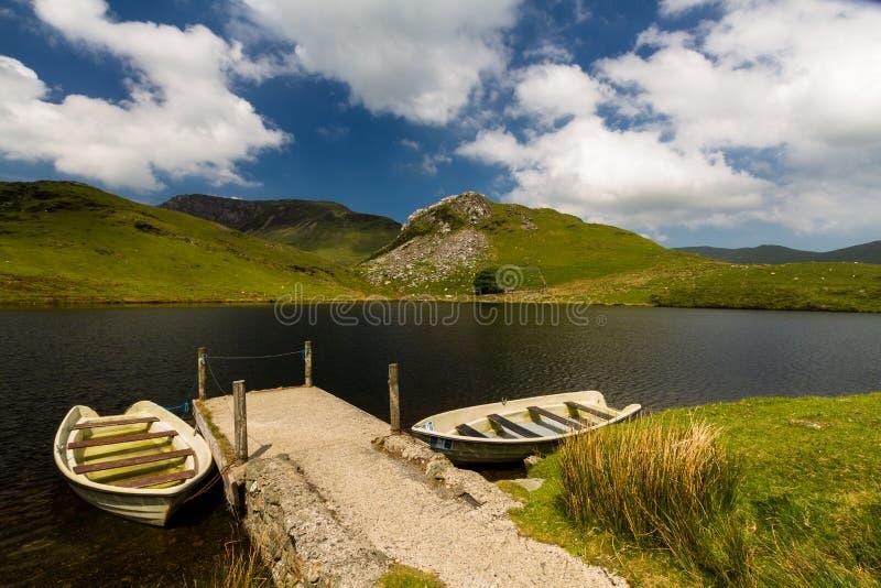 Bacino idrico di Llyn y Dywarchen con due imbarcazioni a remi dal molo, Snowd fotografie stock libere da diritti