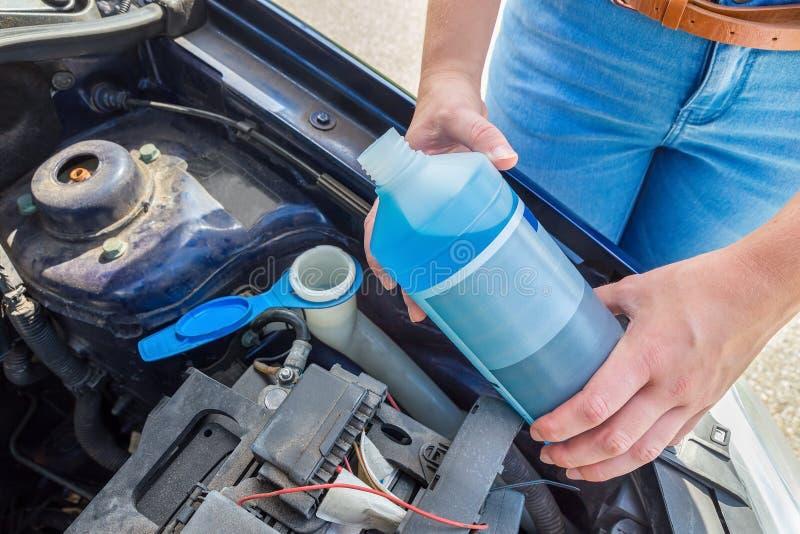 Bacino idrico di riempimento dell'automobile della donna con liquido blu in bottiglia immagine stock