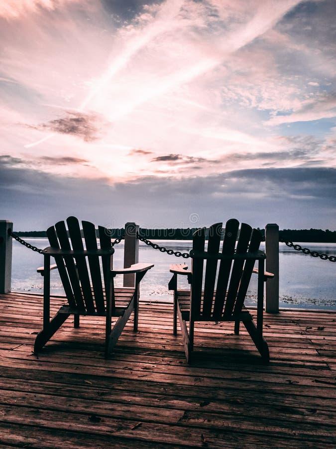Bacino pacifico al tramonto con due sedie di legno vuote immagine stock