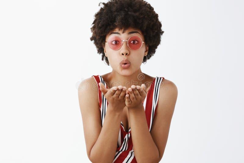 Bacio dolce di salto tenero Ritratto dell'afroamericano sciocco e femminile sveglio in occhiali da sole alla moda ed a strisce immagini stock