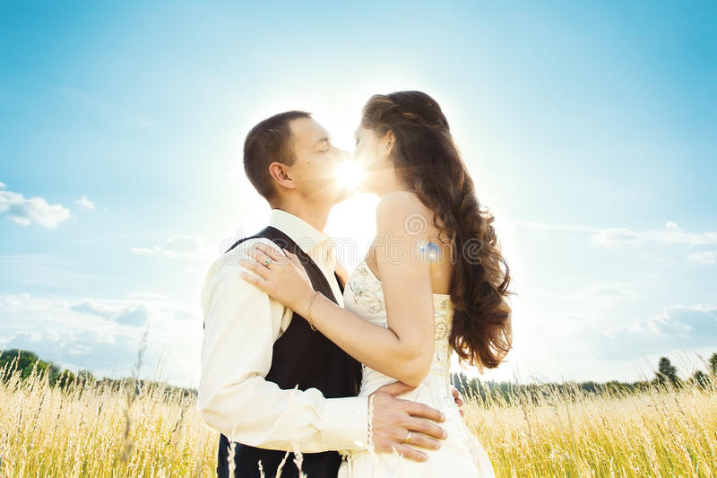 Bacio pieno di sole. sposa e sposo fotografia stock