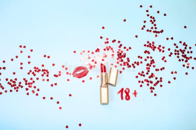 Bacio rosso del rossetto di vista superiore su fondo blu con i coriandoli dei cuori fotografia stock libera da diritti