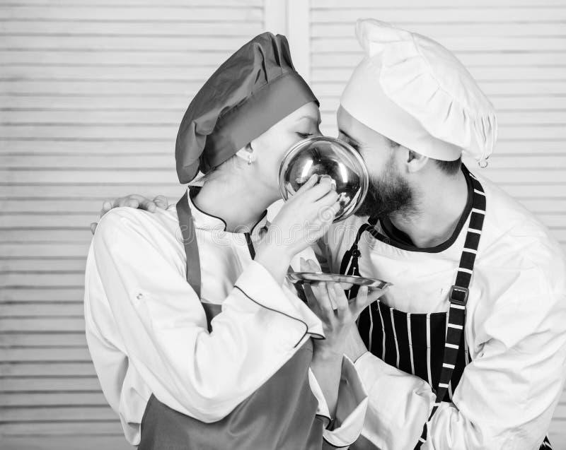 Bacio saporito Famiglia che cucina nella cucina Ingrediente segreto dalla ricetta Uniforme del cuoco cuoco unico della donna e de fotografia stock libera da diritti