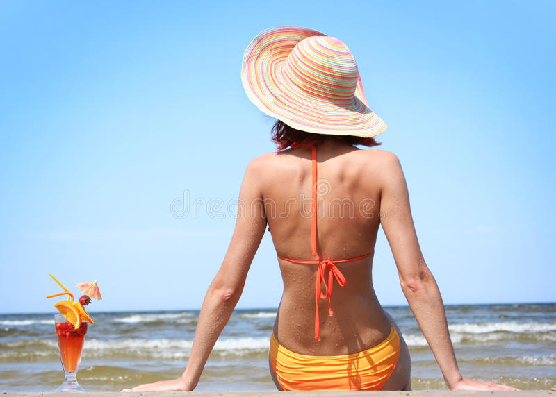 Back. Young woman with fruit cocktail relaxing on beach royalty free stock photo