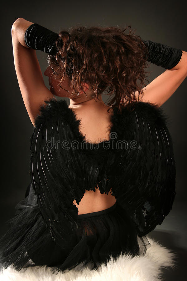 Back. Beautiful young angel with black wings stock photo